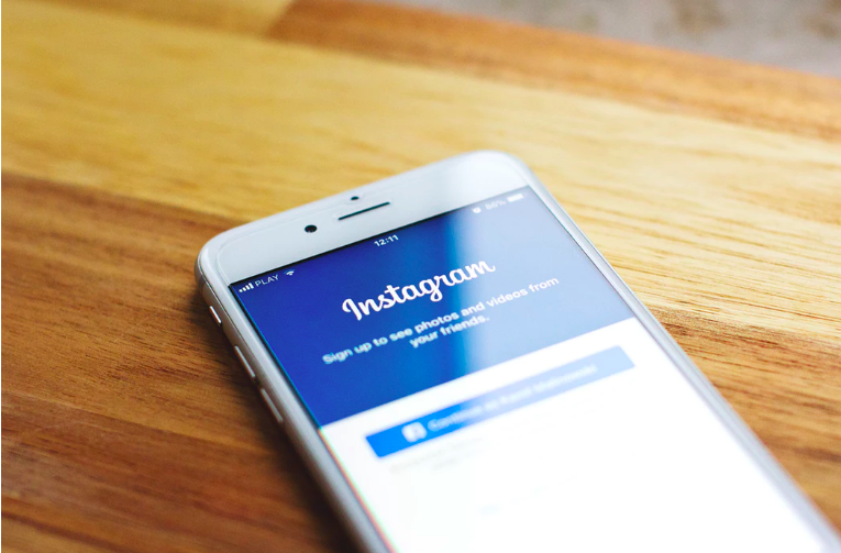 iPhone with the screen showing Instagram login page.