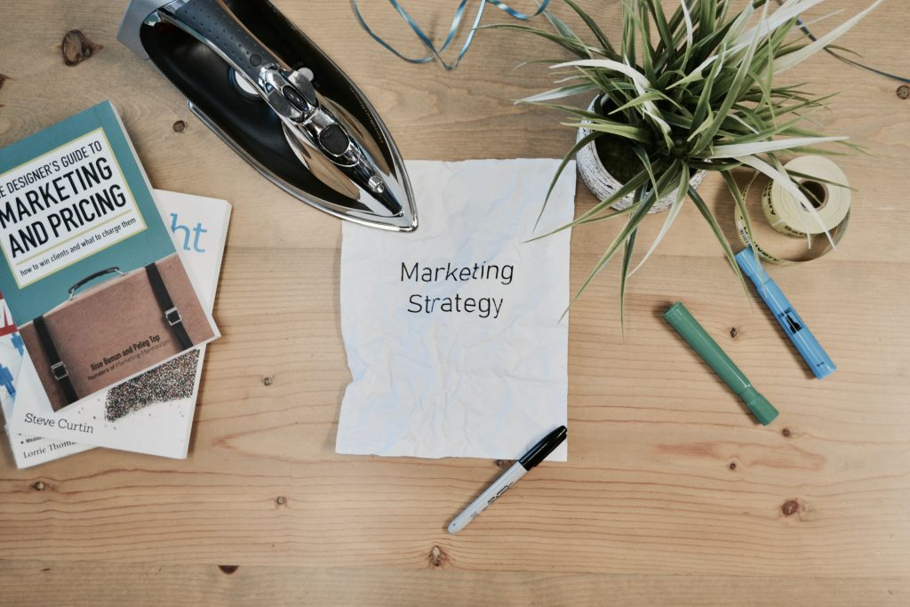 paper that says marketing strategy on a desk surrounded by pens and a marketing and pricing book