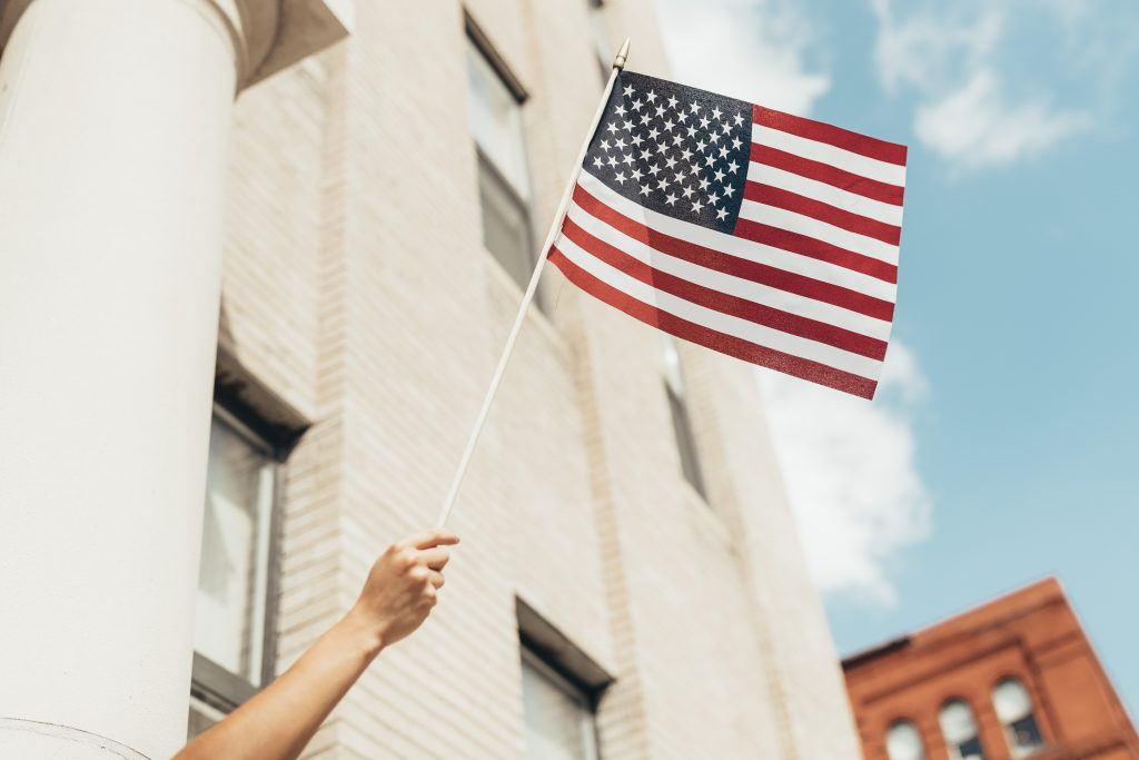 hand holding american flag against blue sky